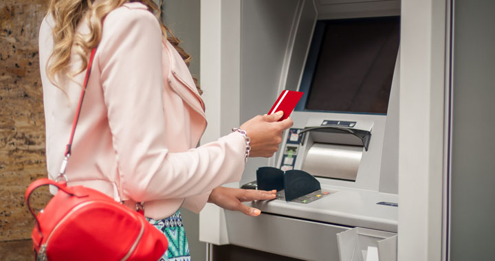woman taking out money from ATM with debit card